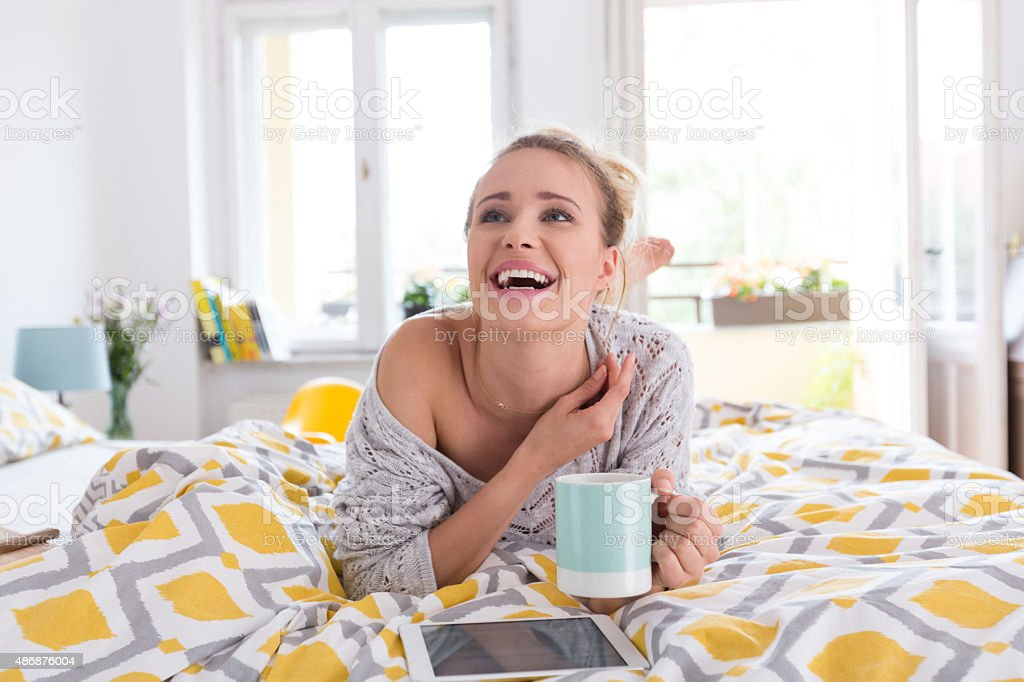 Happy woman resting in bed with coffee and digital tablet stock photo