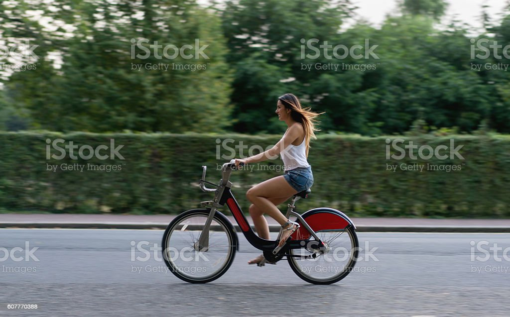 Happy woman riding a bike stock photo