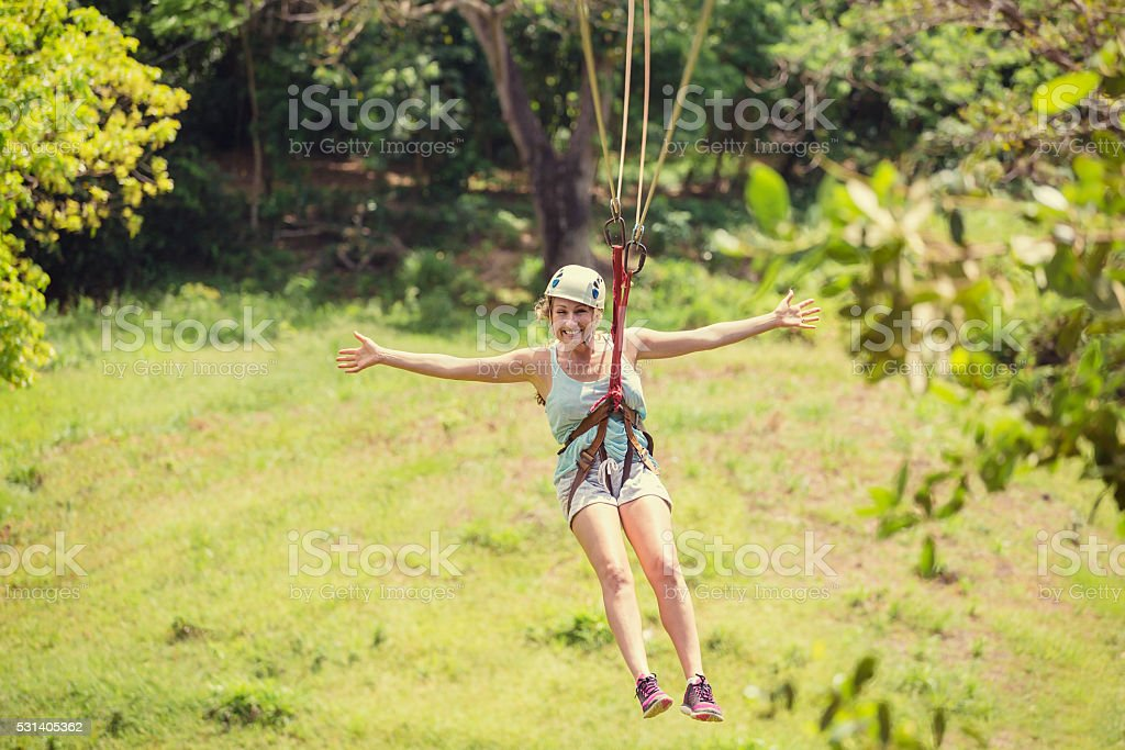 Happy woman riding a zip line in a lush tropical forest stock photo