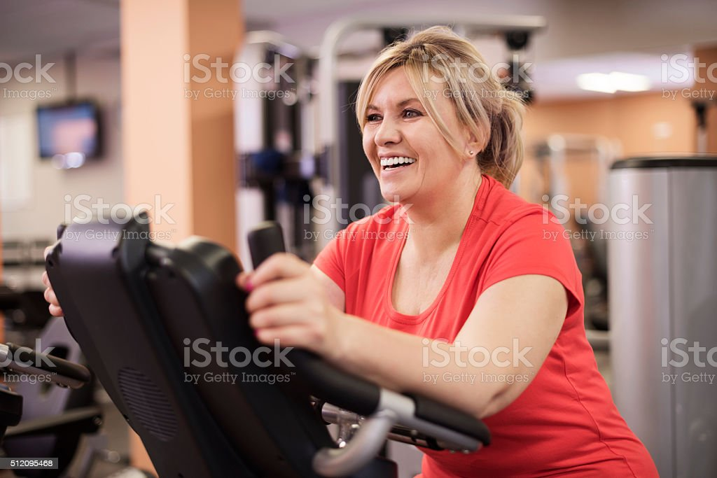 Happy woman riding on exercise bike at the gym stock photo