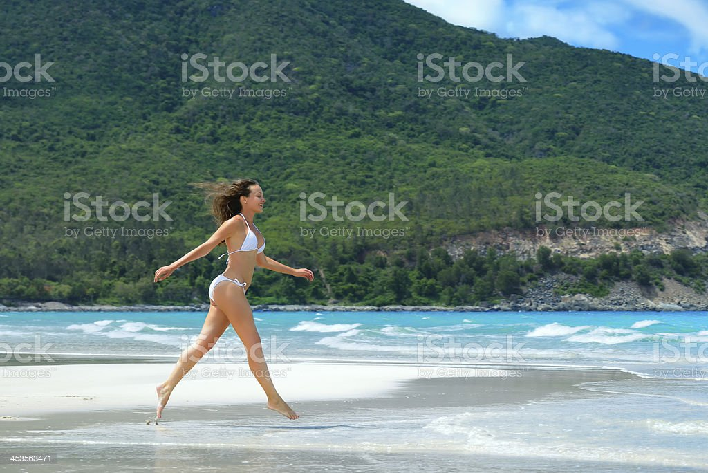 Happy woman running along the white beach royalty-free stock photo