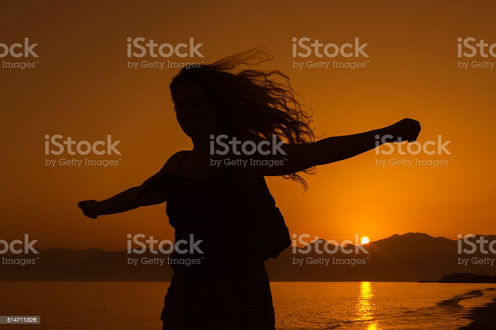 Happy woman running on the beach stock photo