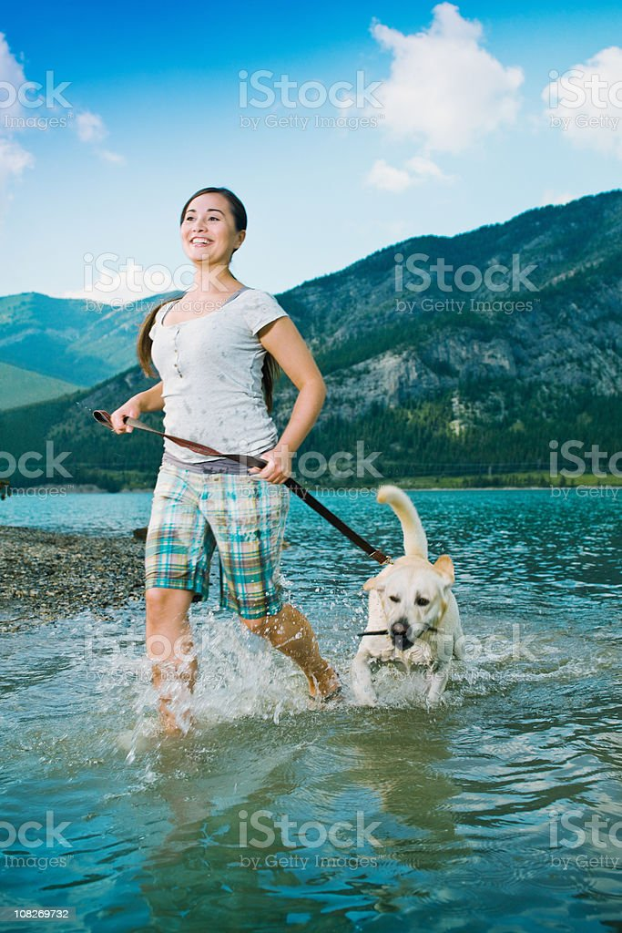 Happy woman running with her dog along lake. royalty-free stock photo