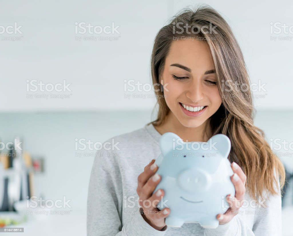 Happy woman saving money in a piggybank stock photo