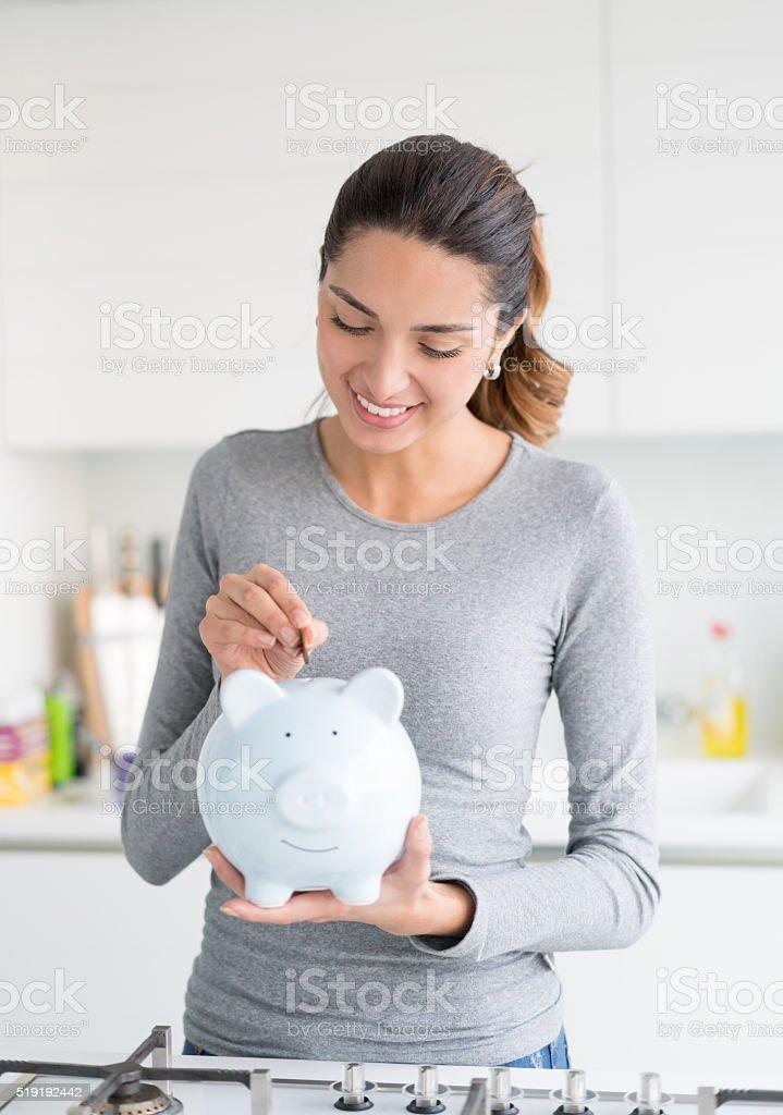 Happy woman saving money in a piggybank stock photo