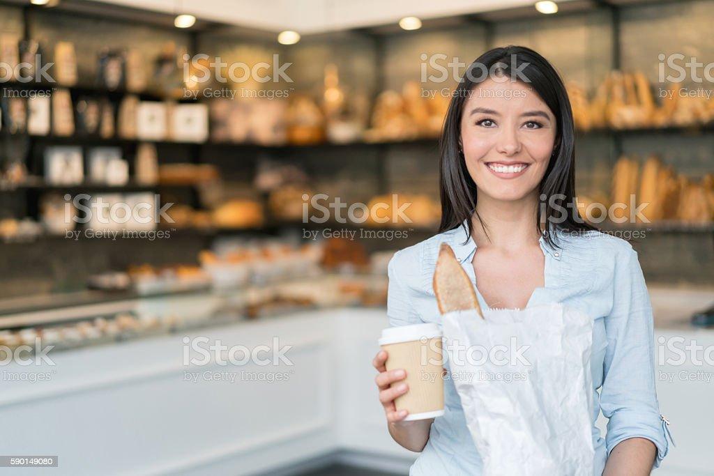 Happy woman shopping at the bakery stock photo