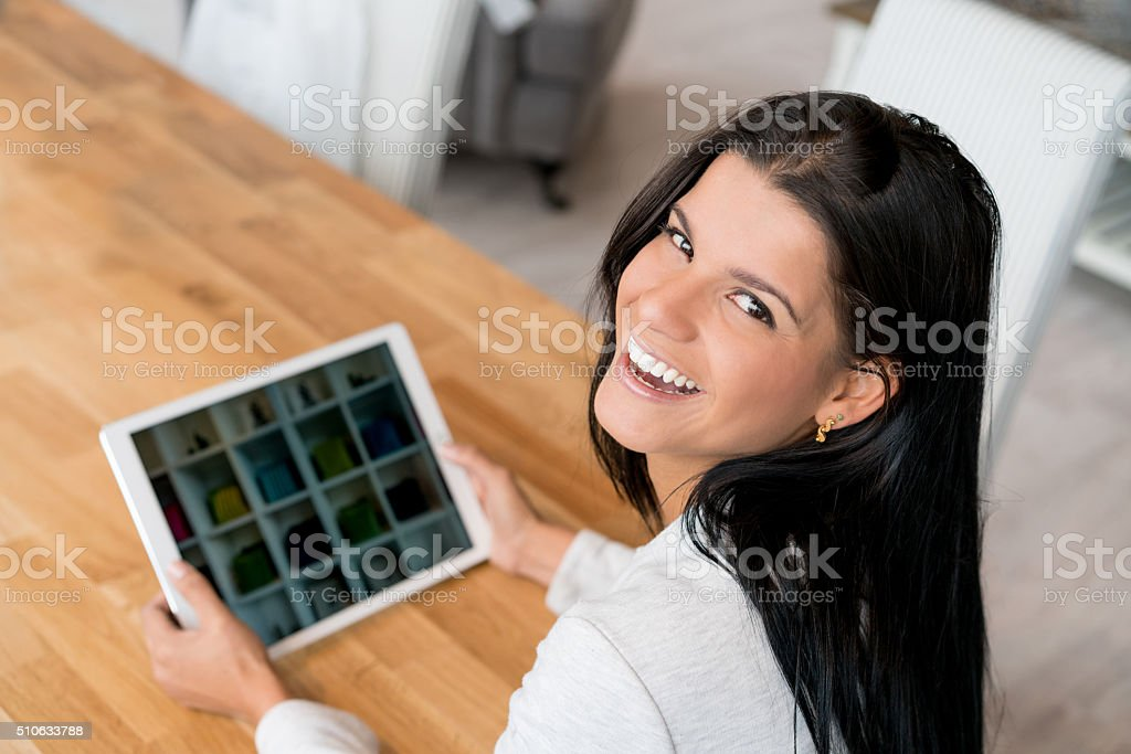 Happy woman shopping online on a tablet computer stock photo