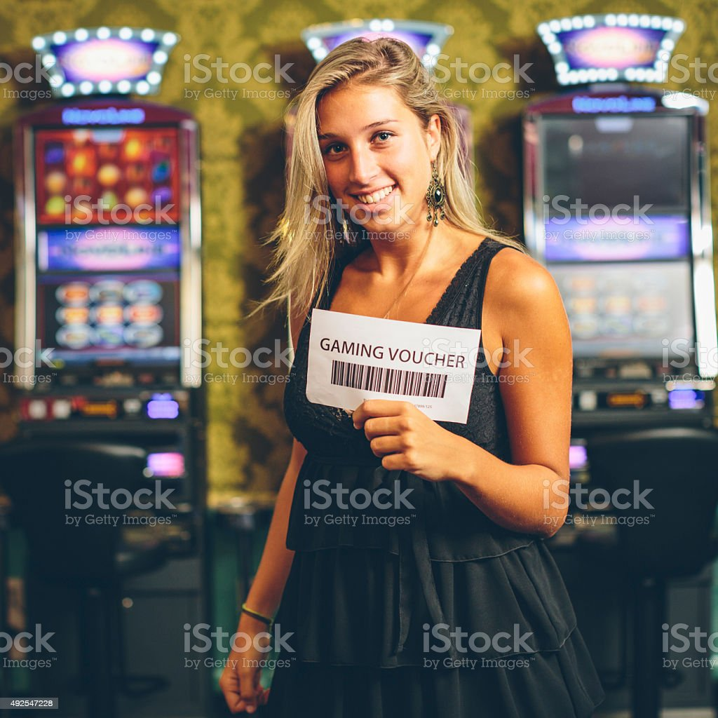 Happy Woman Showing a Gaming Voucher. Slot Machine on the background....