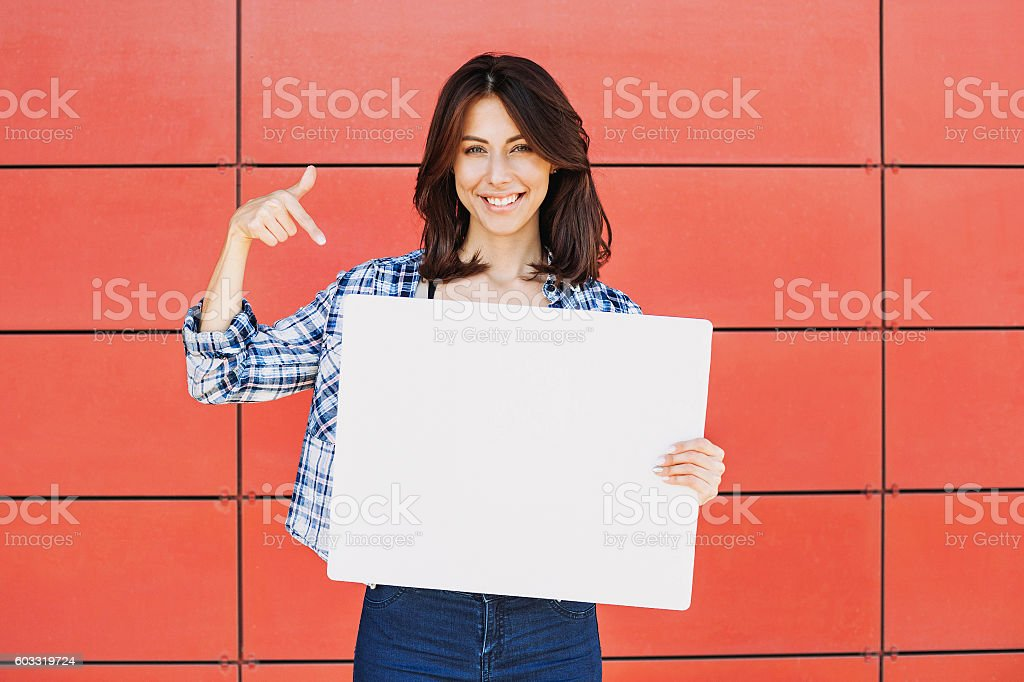 Happy woman showing white banner stock photo
