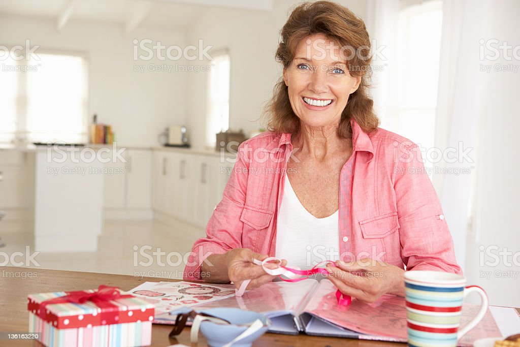 Happy woman sitting at table working on scrapbooking stock photo