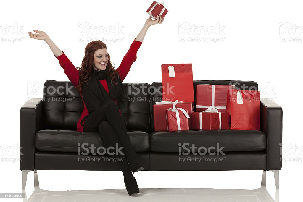 Happy woman sitting on a couch with presents royalty-free stock photo