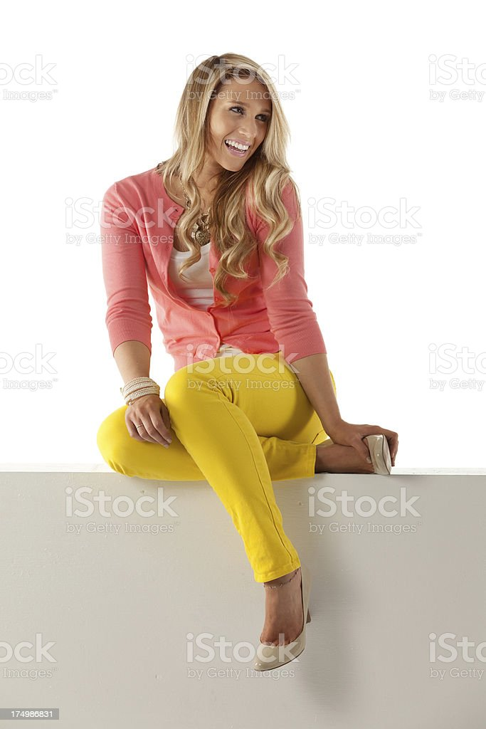 Happy woman sitting on a ledge royalty-free stock photo