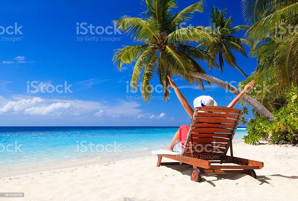 happy woman sitting on beach chair at tropical beach stock photo