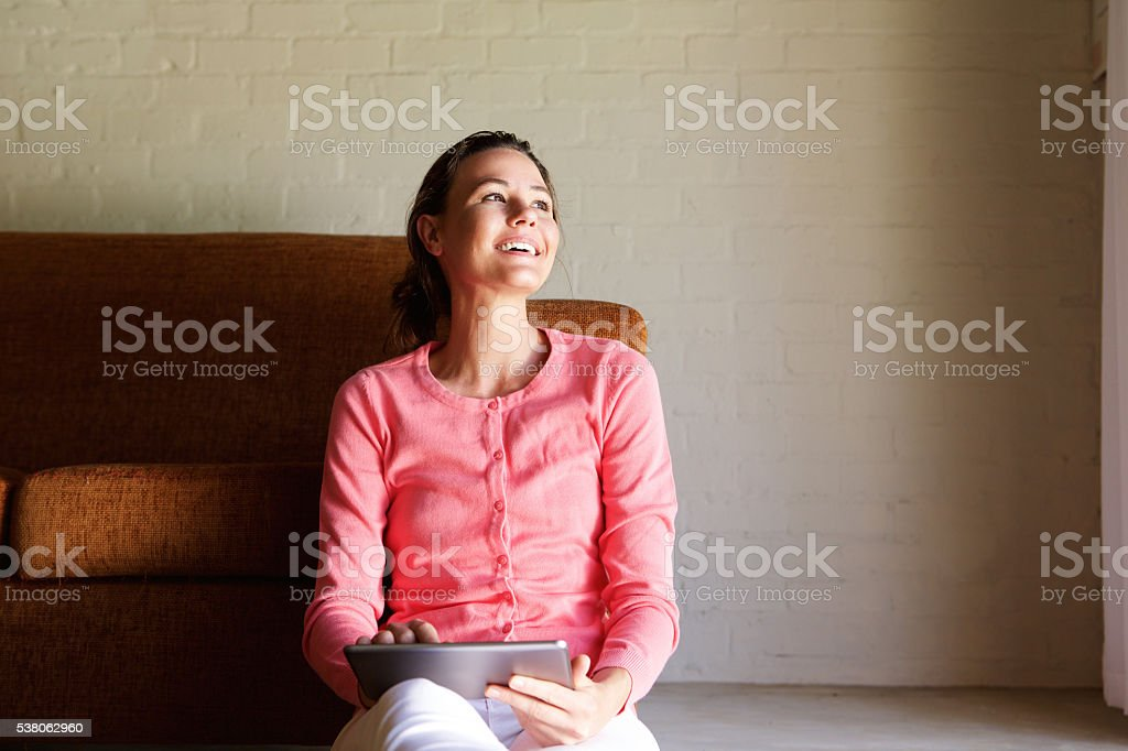 Happy woman sitting on floor with touchscreen tablet stock photo