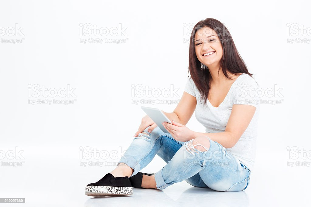 Happy woman sitting on the floor and using tablet computer stock photo