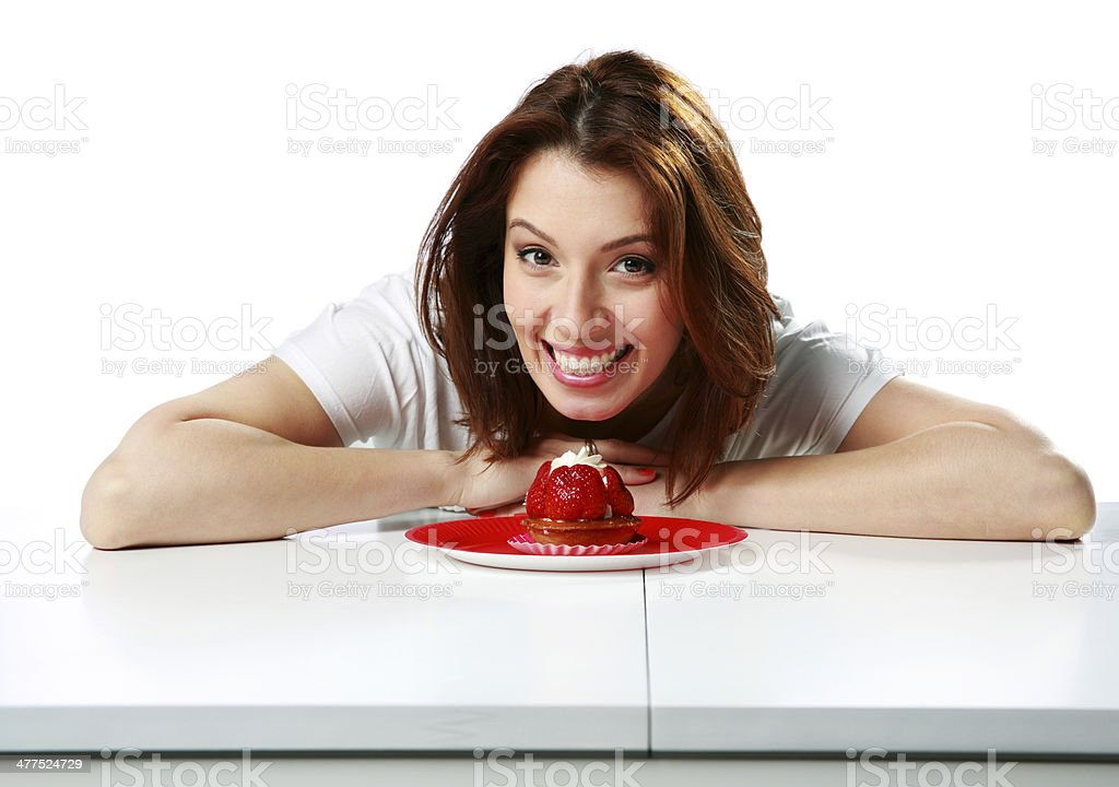 Happy woman sitting on the table with fresh strawberry cake royalty-free stock photo