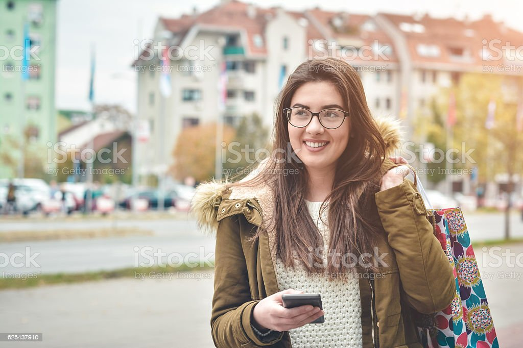 Happy woman smiling and walking in the street stock photo