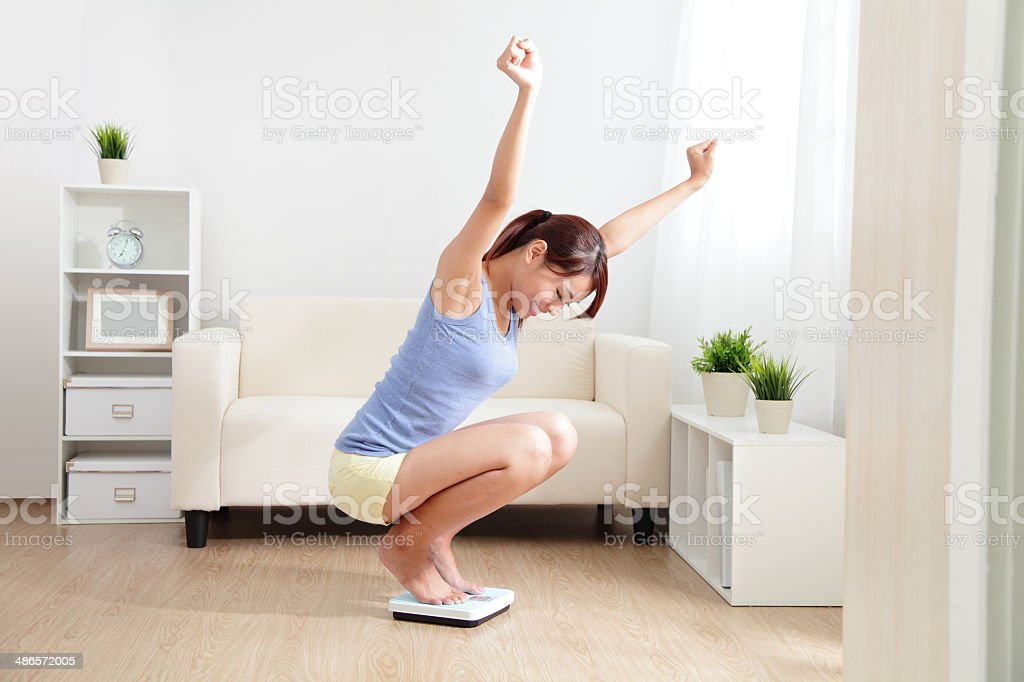 Happy Woman smiling on weighing scales stock photo