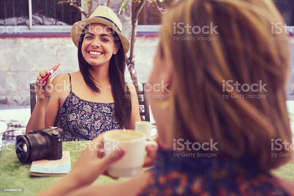 Happy Woman Smoking Electronic Cigarette Drinking Coffee In Bar stock photo
