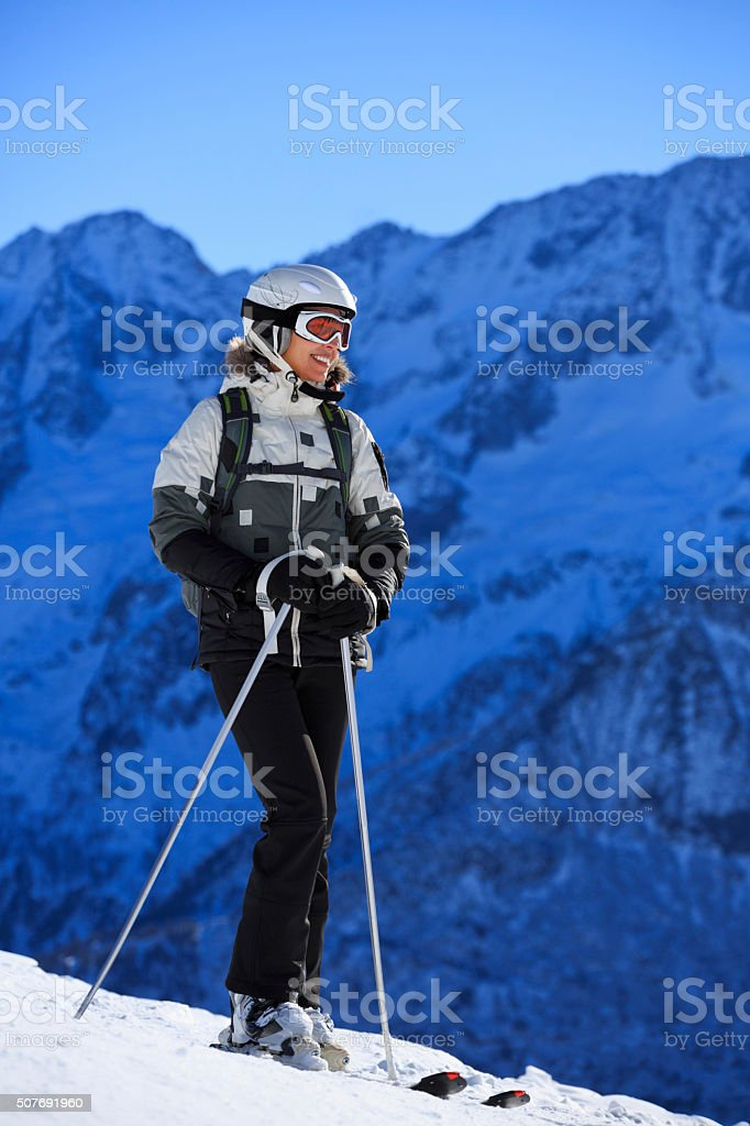 Happy woman snow skier relaxing in sunshine  on ski vacation stock photo