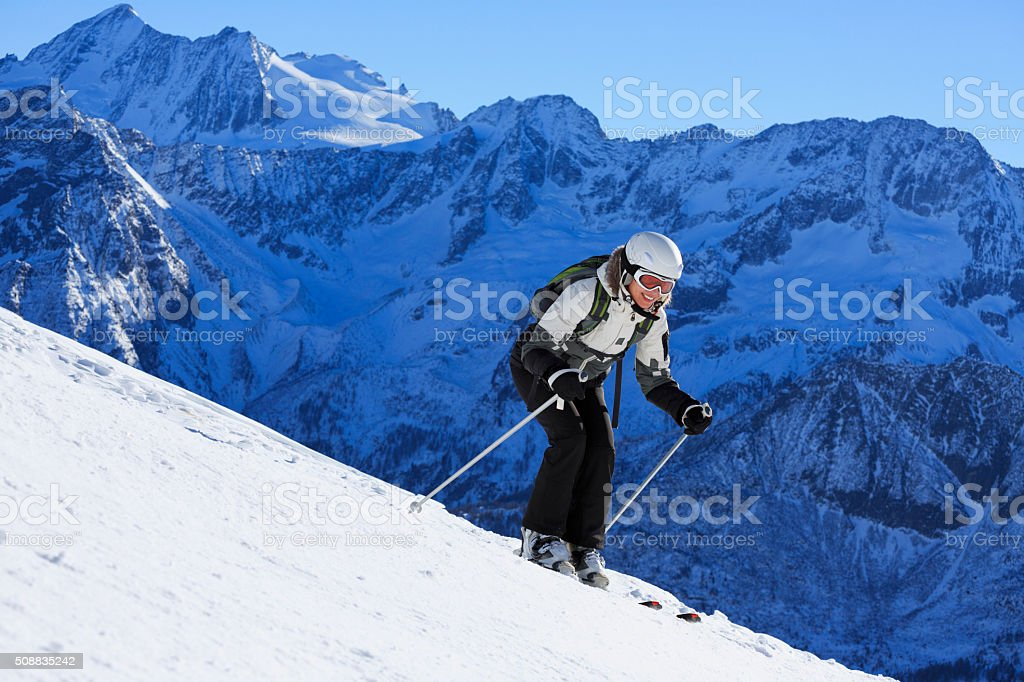 Happy woman snow skier skiing in sunshine  on ski vacation stock photo