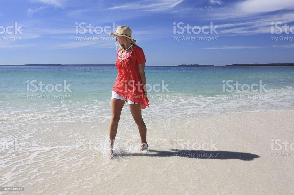 Happy woman splashing feet at the beach stock photo
