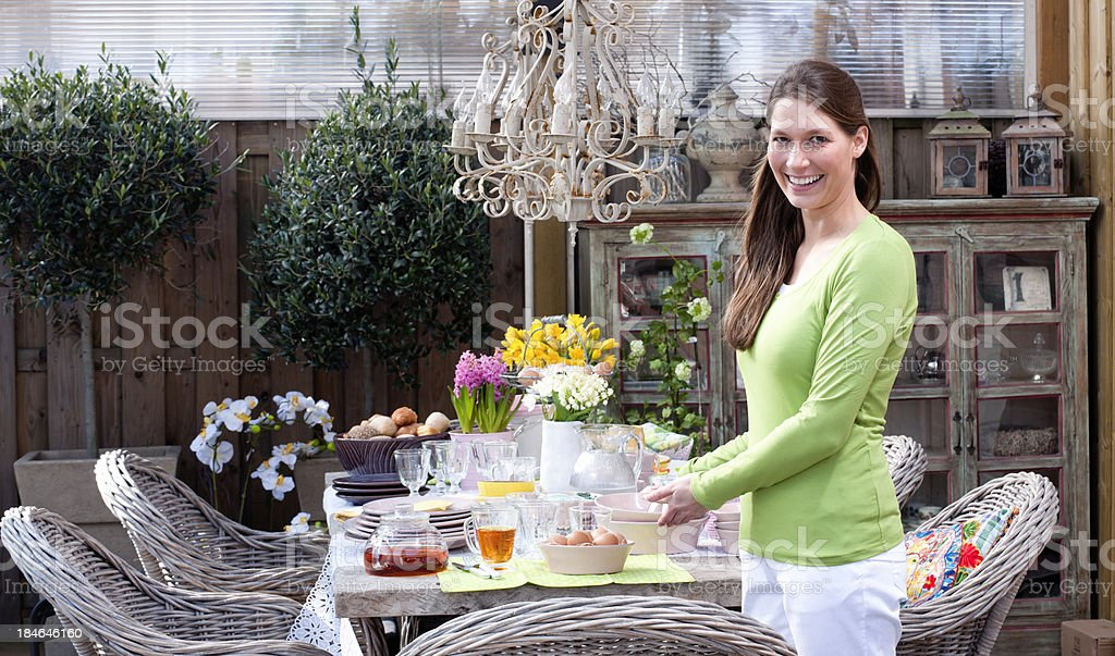 happy woman standing at Easter breakfast picnic table royalty-free stock photo