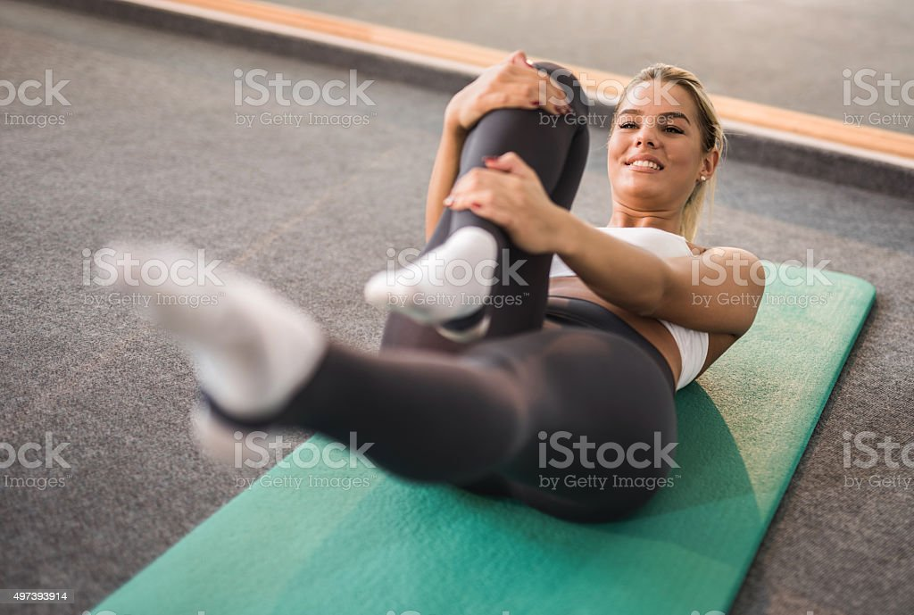 Happy woman stretching during a training class in a gym. stock photo