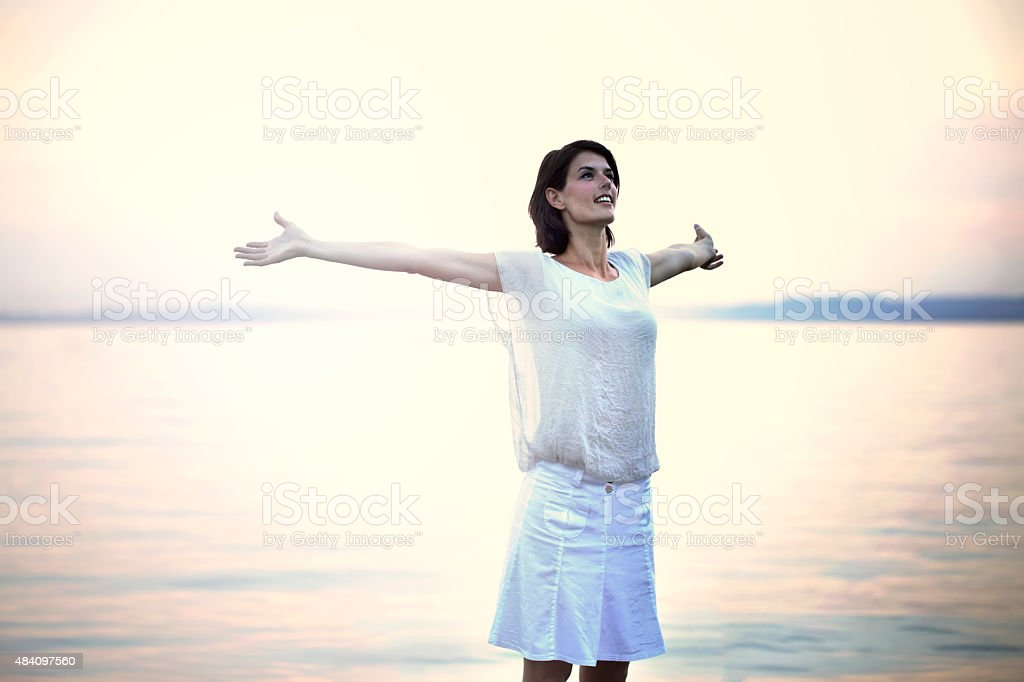 happy woman taking a deep breath at the sunset stock photo