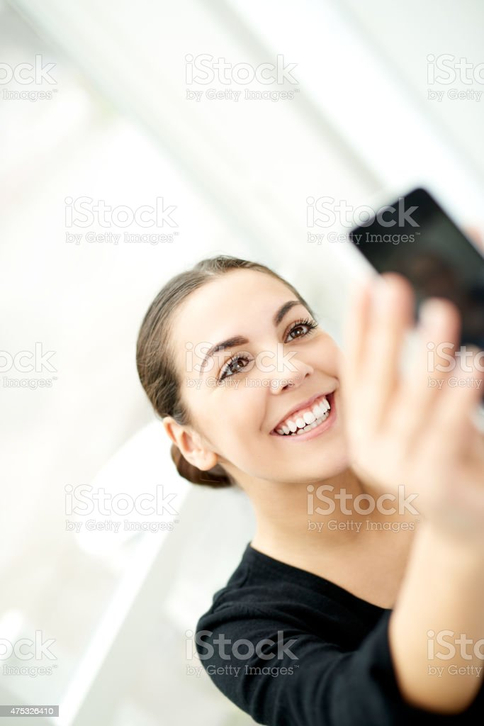 Happy woman taking a selfie on her mobile stock photo