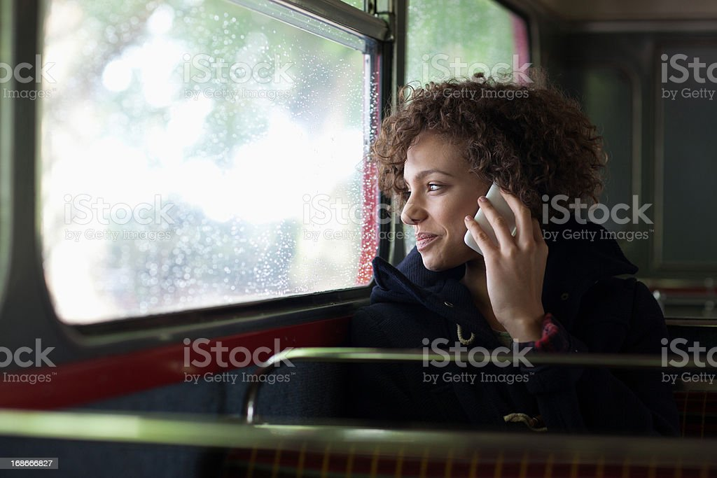 Happy woman talking on cell phone on bus stock photo