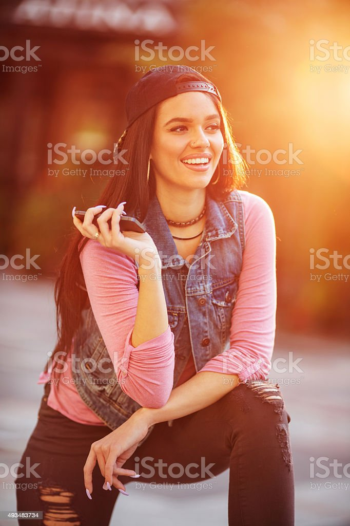 Happy woman talking to someone over cell phone speaker. stock photo