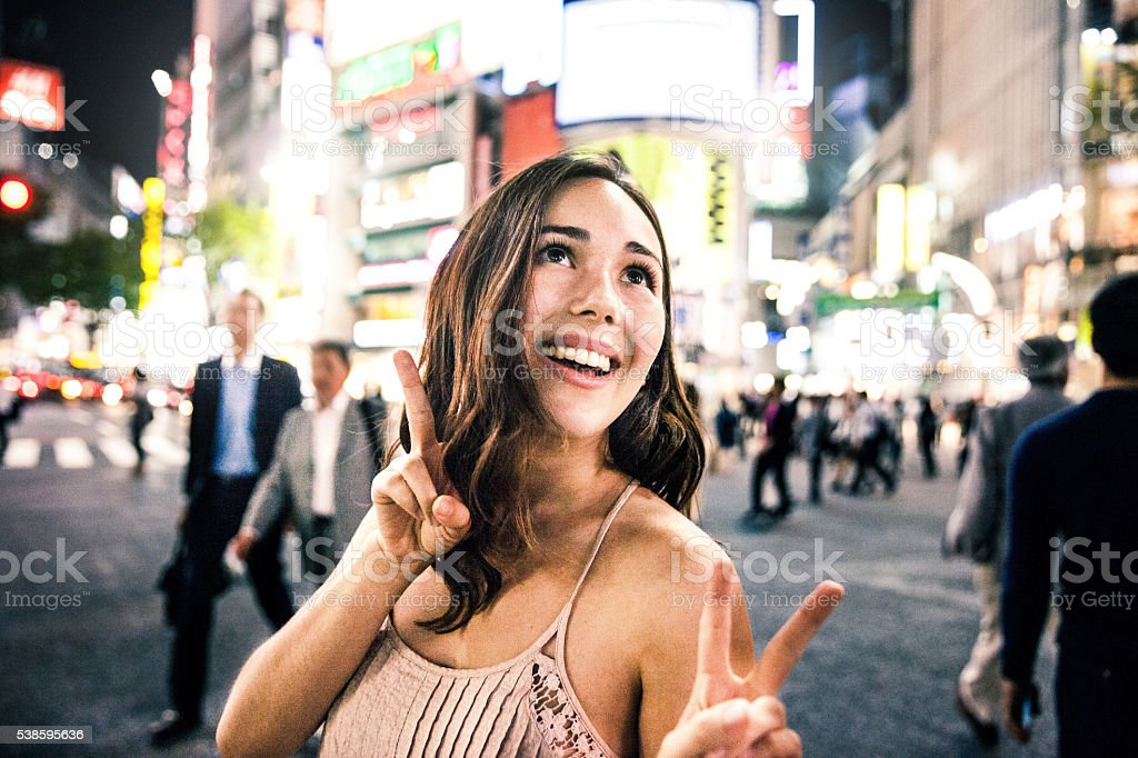 Happy woman travels in Tokyo, Shibuya crossing at night stock photo