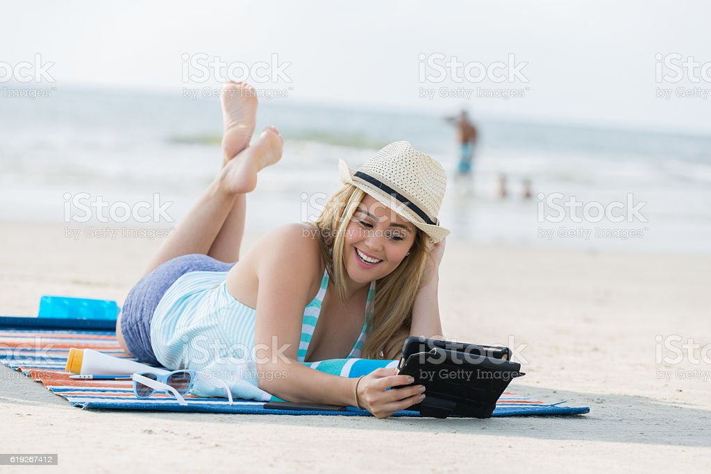 Happy woman uses digital tablet on the beach stock photo