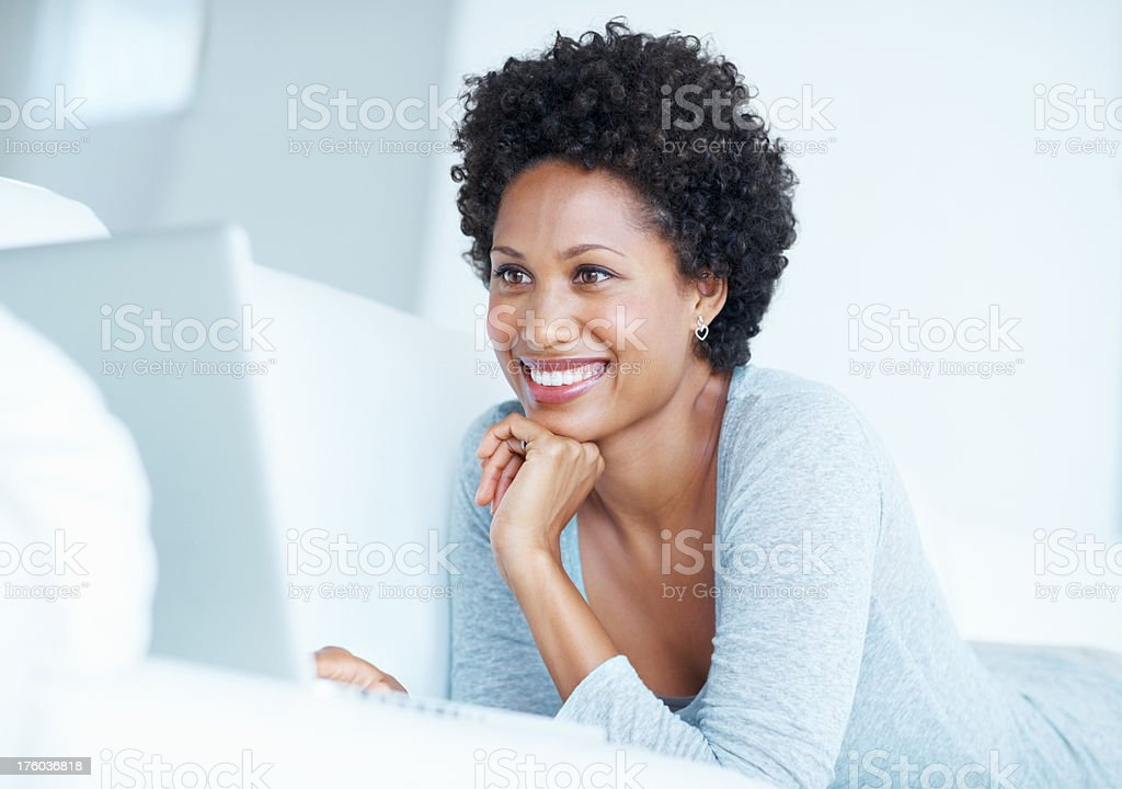 Happy woman using laptop on couch stock photo