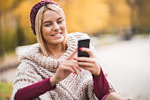 Happy woman using mobile phone during the day in nature.