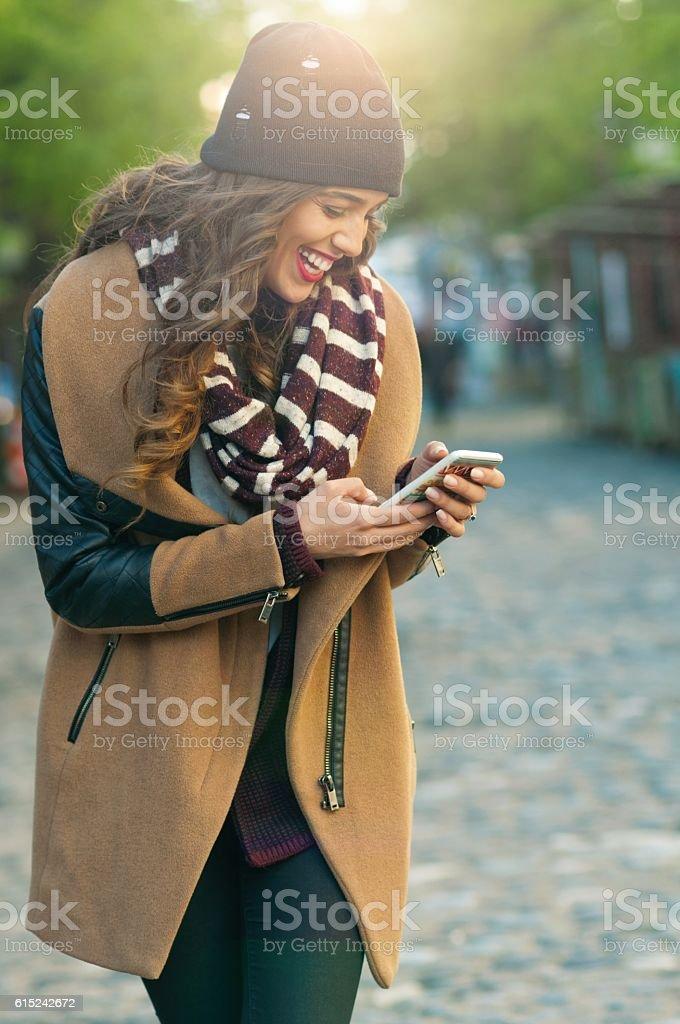 Happy woman using mobile phone, stock photo