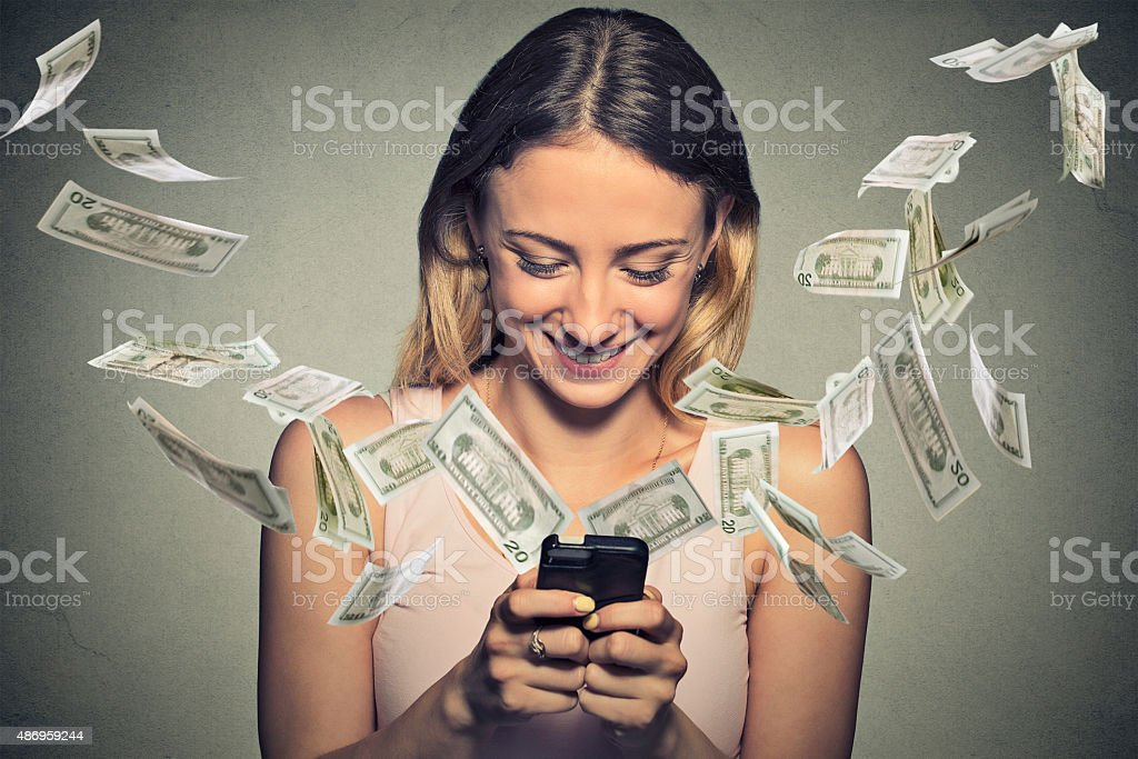 Happy woman using smartphone with dollar bills flying from screen stock photo