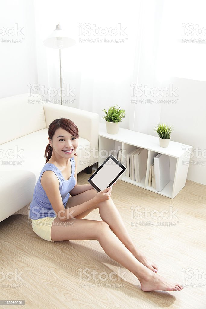 happy woman using tablet pc on sofa royalty-free stock photo