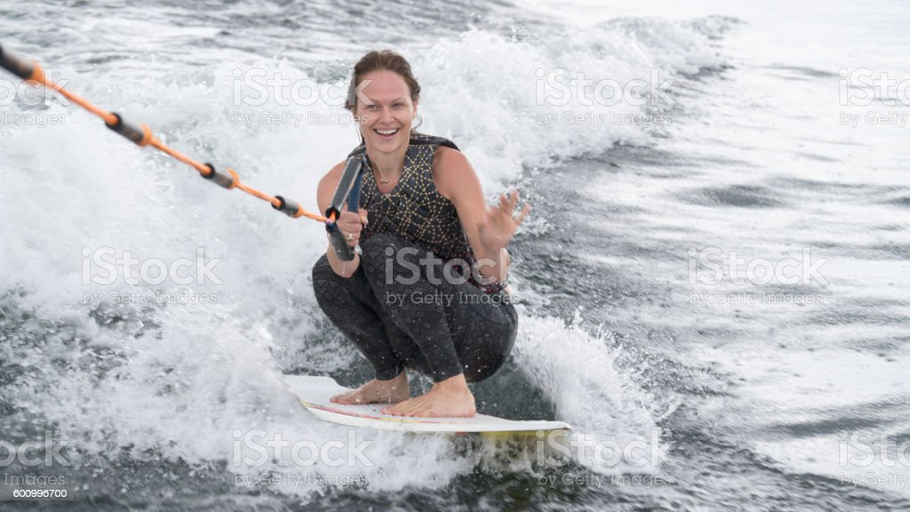 Happy woman wakeboarding, wakesurfing stock photo