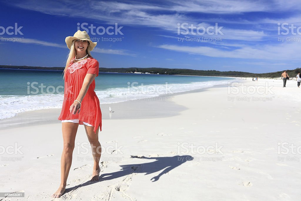 Happy woman walking along beautiful beach stock photo
