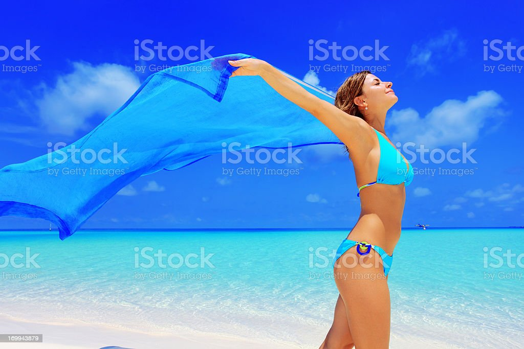 Happy woman walking on a beach with long sarong. royalty-free stock photo