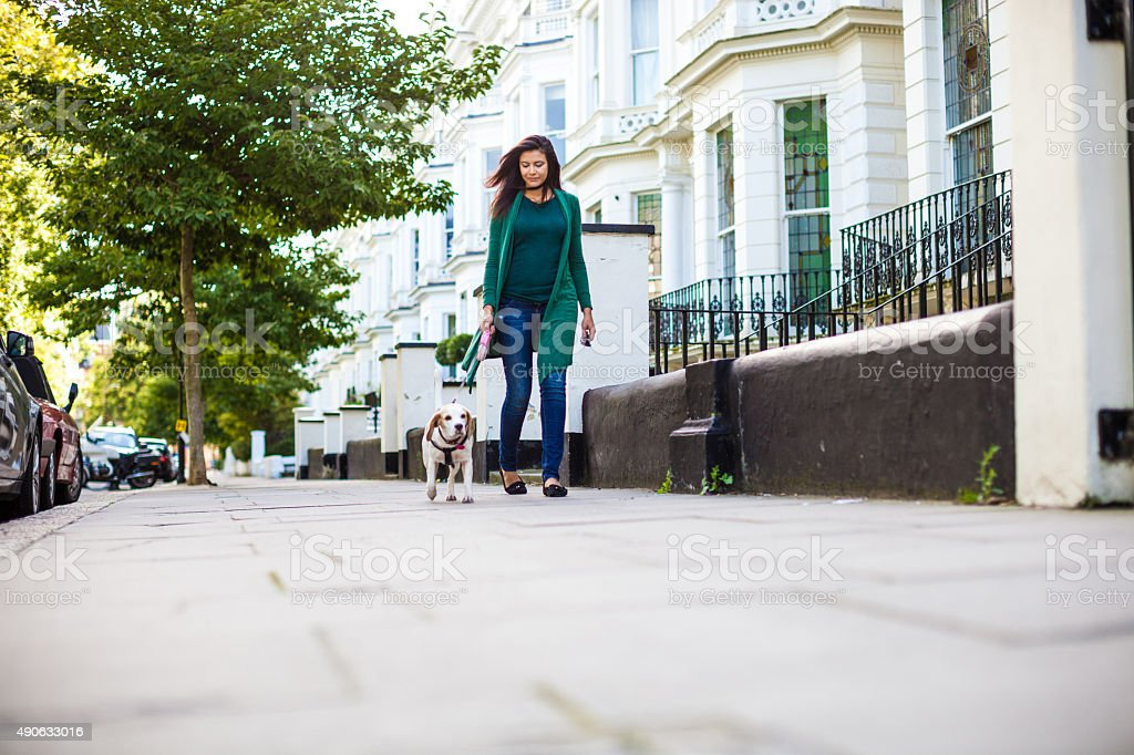 Happy woman walking with dog in early Sunday morning stock photo