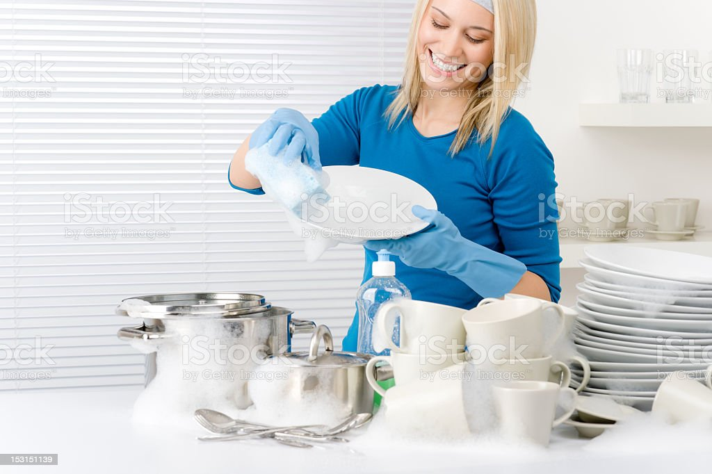 Happy woman washing a large pile of white dishes by hand royalty-free stock photo