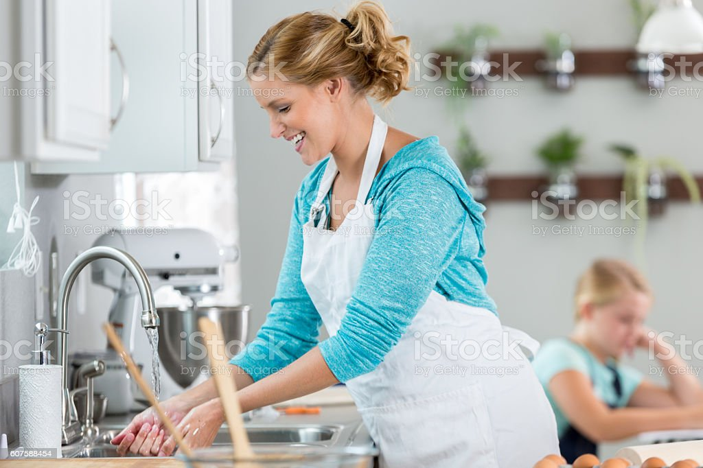 Happy woman washing her hands after baking a pie stock photo