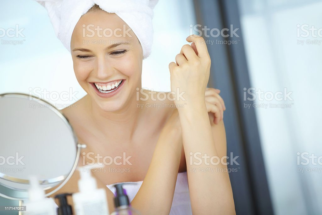Happy woman wearing a bathrobe and looking in the mirror royalty-free stock photo