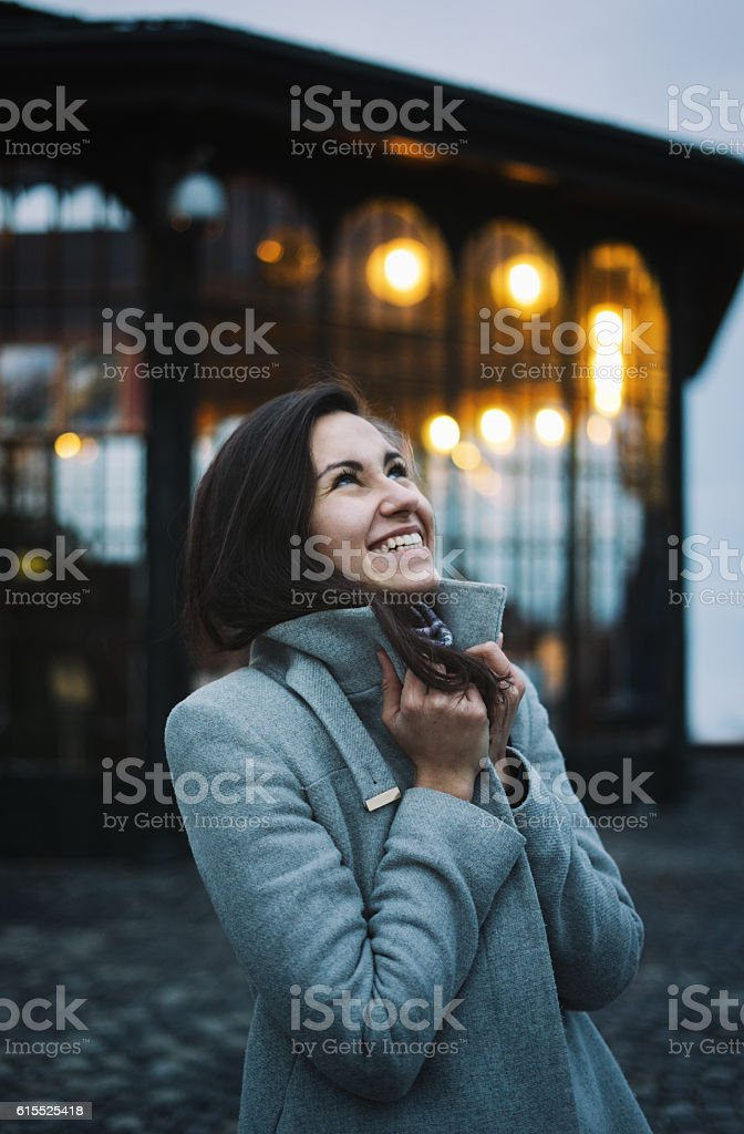 Happy woman wearing coat on the evening street stock photo