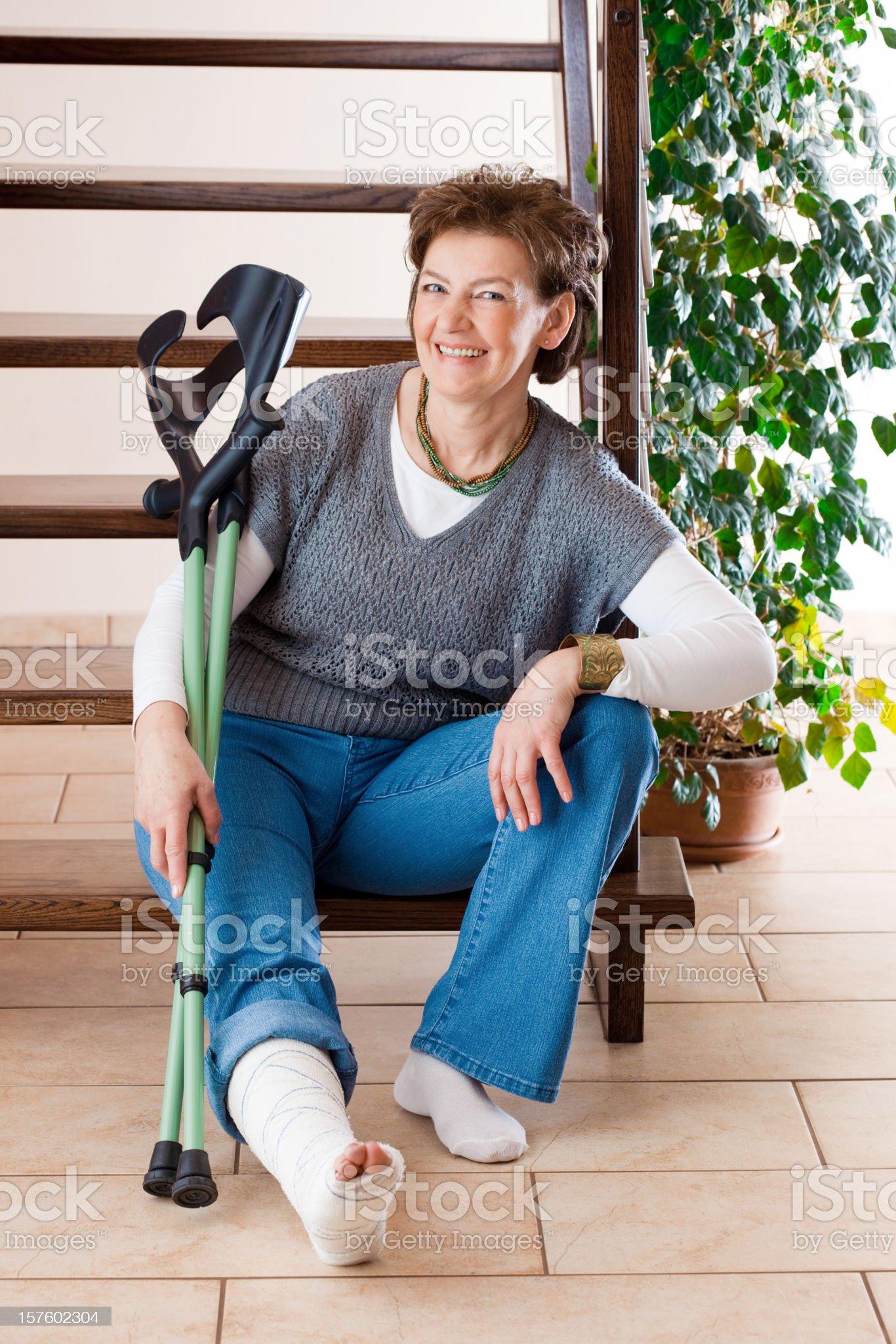 Donna felice con una gamba rotta e le stampelle foto stock royalty-free