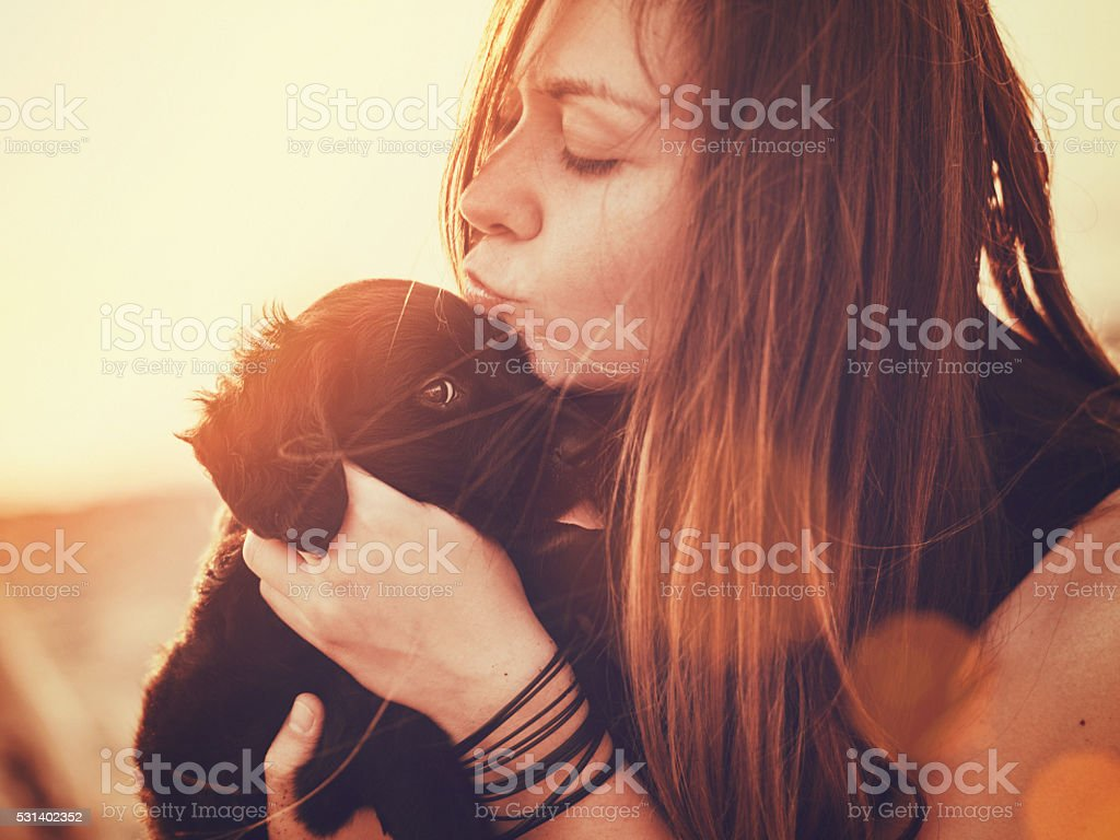 Happy woman with a puppy in her arms stock photo