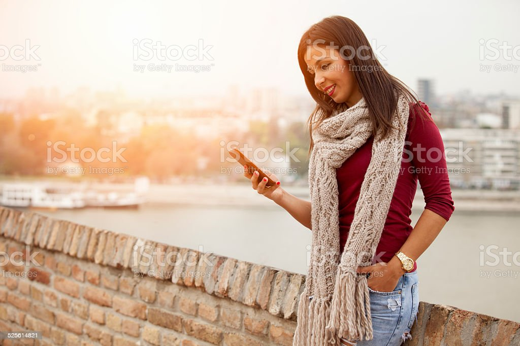 Happy woman with a smart phone outdoors stock photo